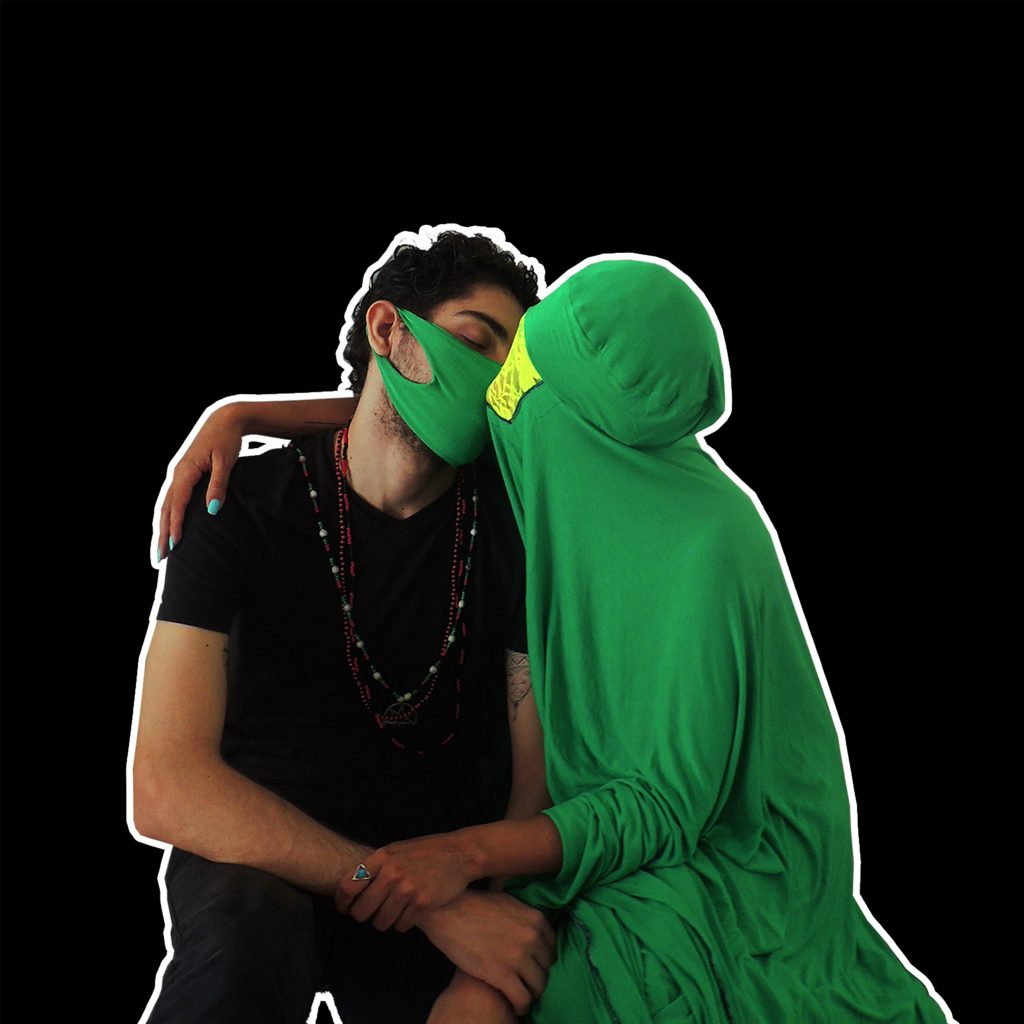 a woman dressed on an body covering green outfit is kissing a man wearing a green mask and dressed in black with some bead chains hanging from his neck.